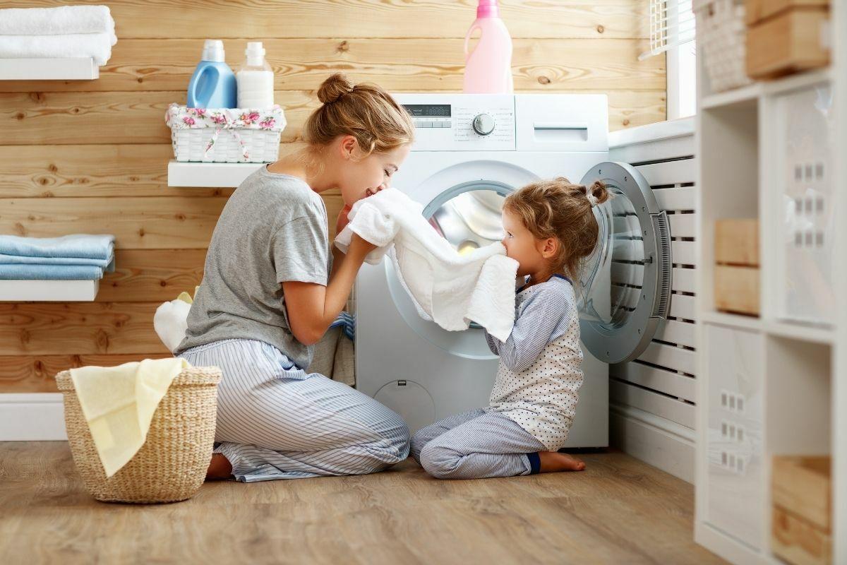 Anya és kislánya a fürdőszobában a friss ruhát szagolja