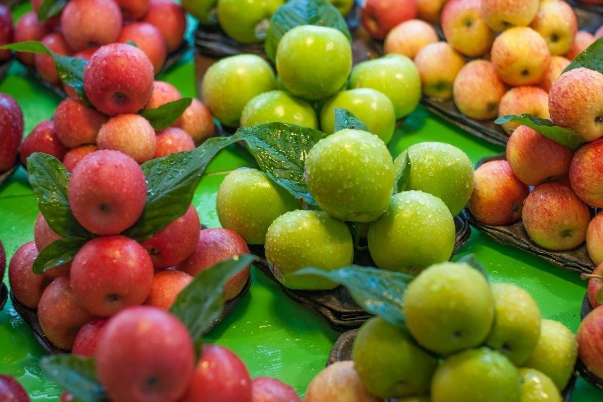 Zöld, piros és sárga almák kupacokba rendezve