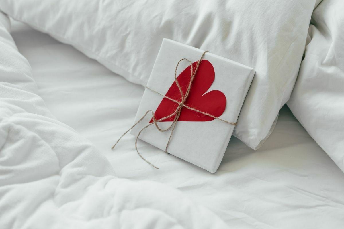 Fehér ágyneműhuzaton becsomagolt, piros szíves ajándék.