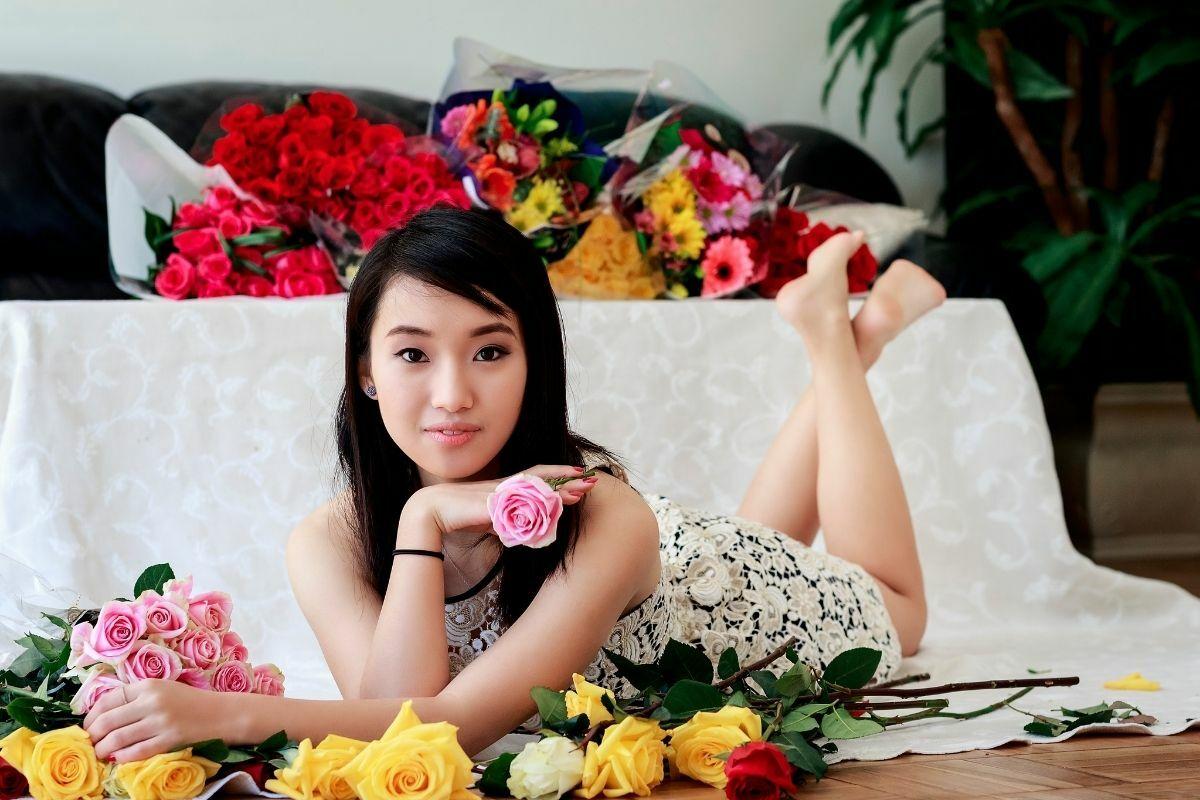 Sok színes virágcsokor az ágyon és előtte egy szép, fiatal nő.